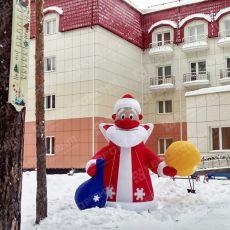Надувной дед мороз в красной шубке с мешками подарков стоит на базе отдыха фото 1
