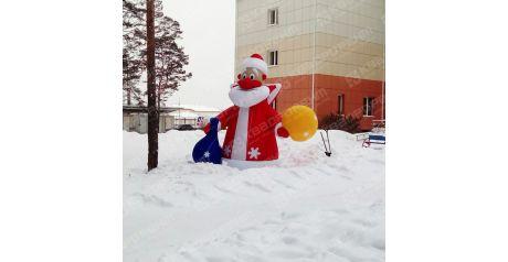 Надувной дед мороз в красной шубке с мешками подарков стоит на базе отдыха фото 2