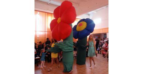 Операторы в надувных цветочных костюмах на мероприятии в школе